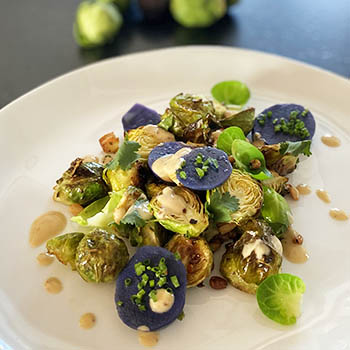 Grilled Brussels sprouts, with velvet potatoes, roasted pine nuts, tahini sauce with olive oil and fresh coriander
